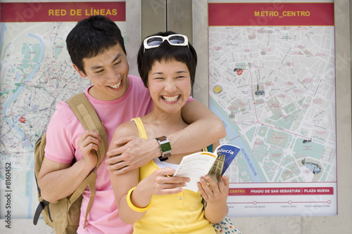 Man embracing woman with leaflet by maps on wall, smiling, close-up