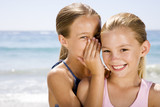 A young girl whispering to her friend on the beach