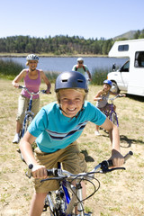 Family of four on bicycles by motor home, close-up of boy (10-12)