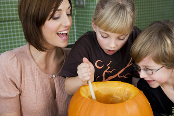 Little girl and boy making a pumpkin lantern with their mother.