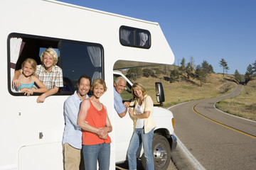 Family of three generations with motor home, smiling, portrait