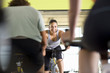 Fitness instructor leading class on exercise bicycles in gym, low angle view
