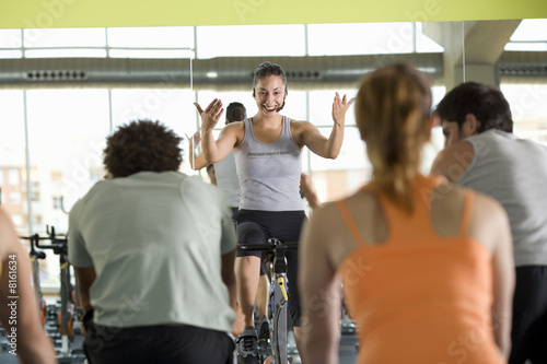 Fitness instructor leading class on exercise bicycles in gym, rear view