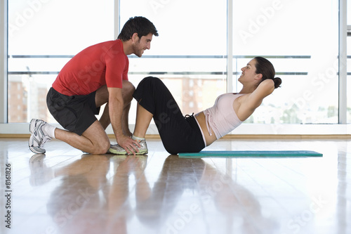 Man helping woman with sit-ups in gym studio, side view