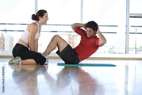 Woman helping man with sit-ups in gym studio, side view
