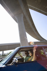 Young couple in car beneath overpass, smiling (lens flare)