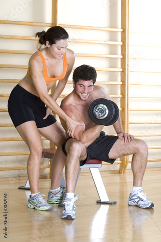 Woman feeling biceps of bare chested man lifting weights in gym, smiling