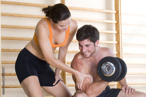 Woman feeling biceps of man using dumbbell, close-up