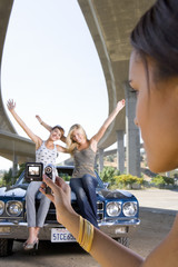 Young woman taking photograph of friends on bonnet of car beneath overpass, close-up
