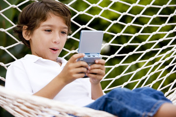 little boy playing electronic game sitting in hammock