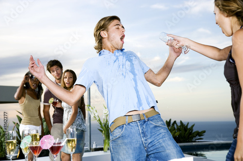 Woman throwing her drink over a man at a party
