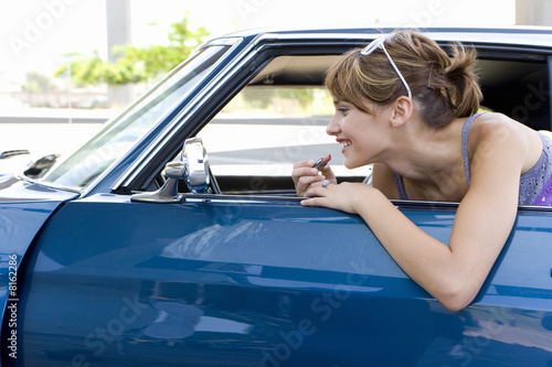 Young woman leaning on open door of car applying lipstick in rear view mirror, side view