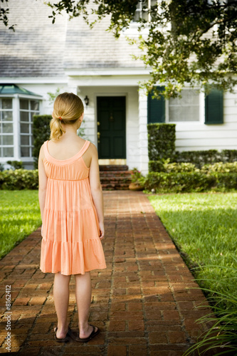 Little girl standing on the garden path outside her new home