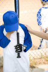 Adult comforting child at little league baseball game