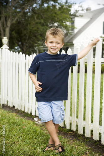 little boy standing by picket fence