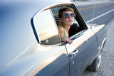 Young woman in sunglasses in car, looking out window