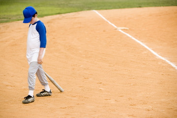 Young boy walking off baseball pitch
