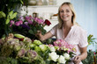 Woman florist in her shop, surrounded by an assortment of flowers