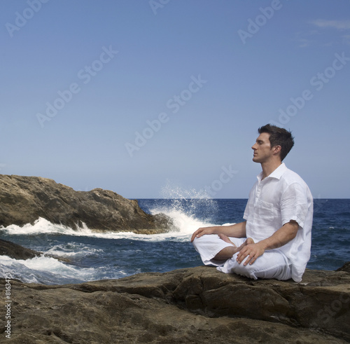 A man meditating by the sea