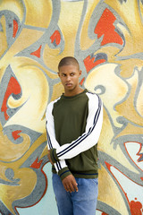 Portrait of a young African American man in front of a graffiti covered wall