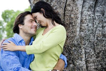 couple embracing in front of tree