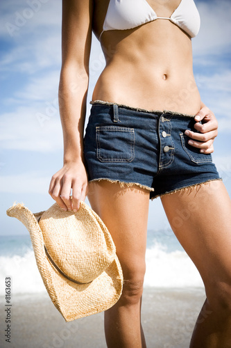 A young woman on the beach bikini and shorts
