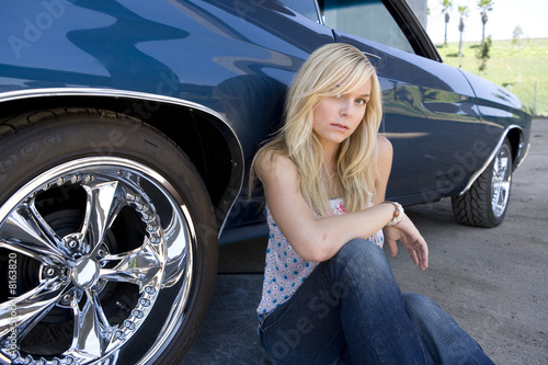 Young woman crouching by car, portrait