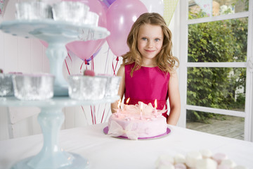 little girl standing in front of birthday cake on tea table