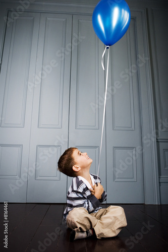 little boy sitting on the floor holding a balloon