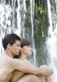 A couple sitting by a waterfall