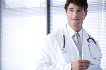 Male doctor in a white coat smiling