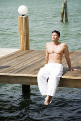 Topless man sunbathing on a jetty