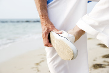 Close up of a senior man putting on his shoes on a beach