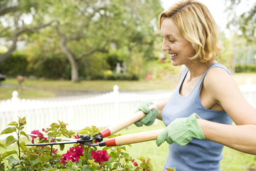 woman pruning plant with garden shears