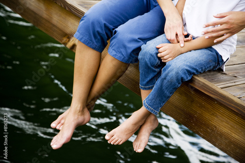cropped image of woman and child sitting on jetty