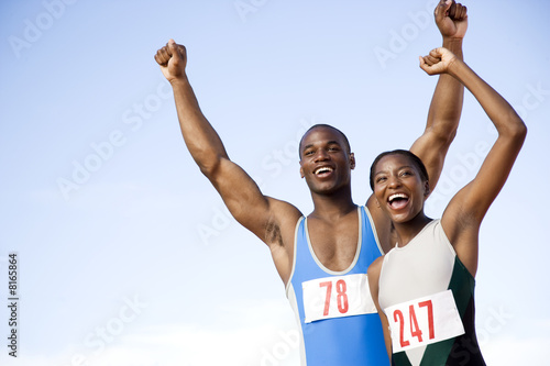 Portrait of a female and athletes with their arms in the air