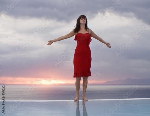 A woman standing on the edge of a pool at sunset