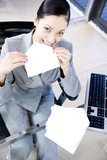 Businesswoman licking and sealing an envelope