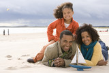 Family of three with toy boat on beach, smiling, portrait
