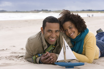 Young couple with toy boat on beach, smiling, portrait
