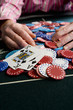 Man collecting pile of gambling chips on table, close-up of winning cards