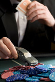 Man placing model car on pile of gambling chips on table, mid section