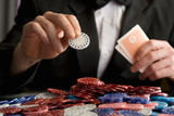 Man placing gambling chip on pile of chips on table, mid section