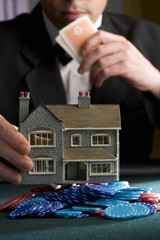 Man placing model house on pile of gambling chips on table, mid section