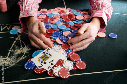 Man collecting pile of gambling chips on table, close-up