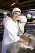 Female baker kneading dough, smiling, portrait