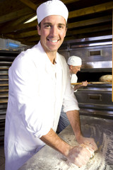 Baker kneading dough, smiling, portrait