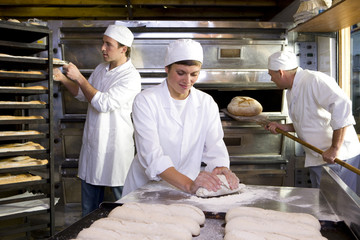 Female baker kneading dough, colleagues in background