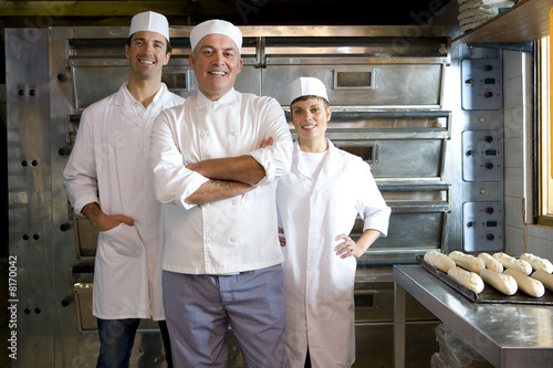 Bakers by tray of baguettes, smiling, portrait
