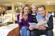 Young couple in furniture shop, daughter (6-8) embracing parents with brochure, smiling, portrait